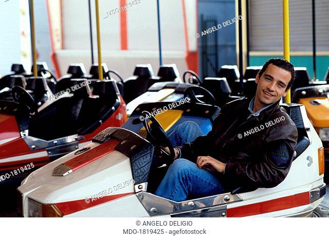 Italian singer-songwriter Eros Ramazzotti having fun on a bumper car. Italy, 1990