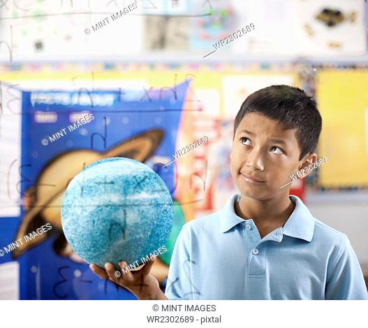 A boy holding a globe, standing by an equation board, looking puzzled and pensive