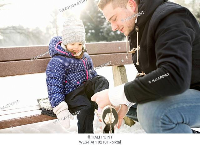 Father helping daughter to put on her ice skates