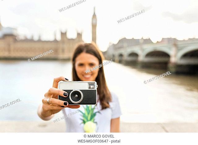 UK, London, woman holding old-fashioned camera near Westminster Bridge
