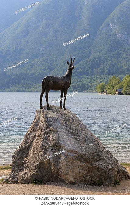 Gold Horned Chamois statue with Bohinj lake in background, Slovenia