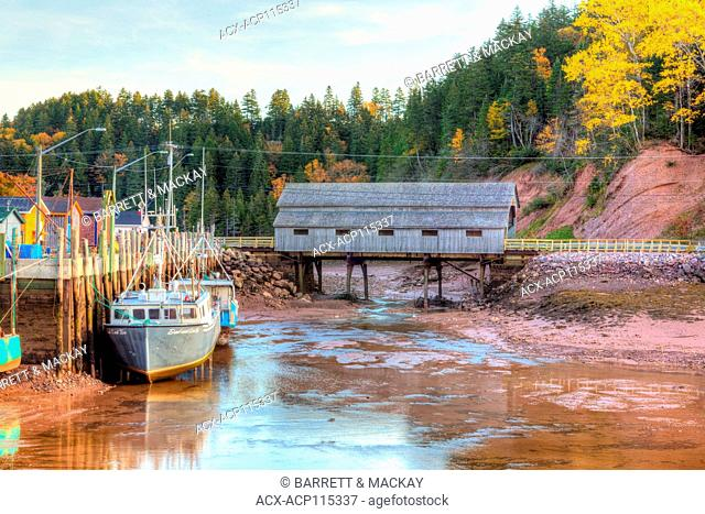 Fishing boats and covered bridge at low tide, Bay of Fundy, St. Martin's, New Brunswick, Canada
