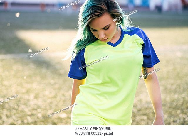 Portrait of young woman in jersey on football ground looking down