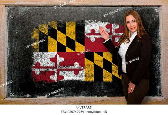 Successful, beautiful and confident woman showing flag of maryland on blackboard for marketing research, presentation and tourist advertising