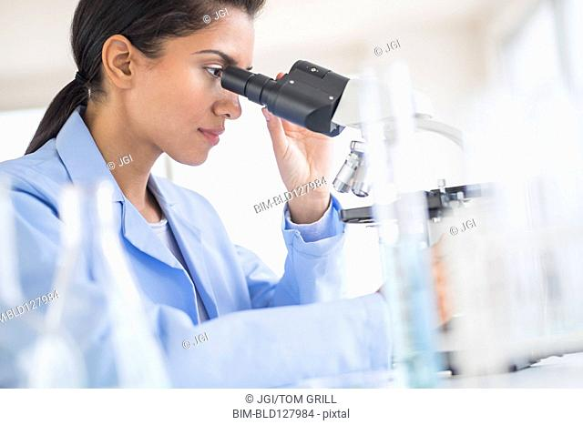 Hispanic scientist using microscope in laboratory