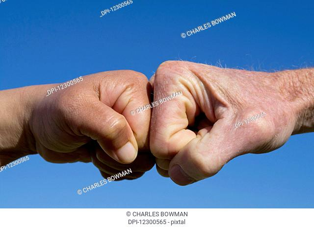 Fists pound against each other on a blue background; Spain