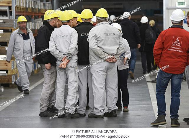 30 November 2018, Mecklenburg-Western Pomerania, Wolgast: After the works meeting, shipyard workers stand in the equipment hall of the Peene shipyard belonging...
