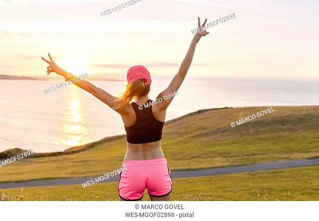Young woman looking at the sea after workout with arms out