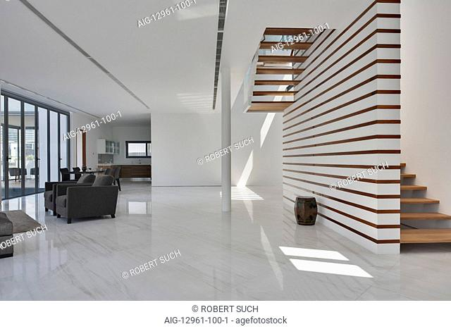 Modern house. Spacious white open-plan living area and wooden stairs