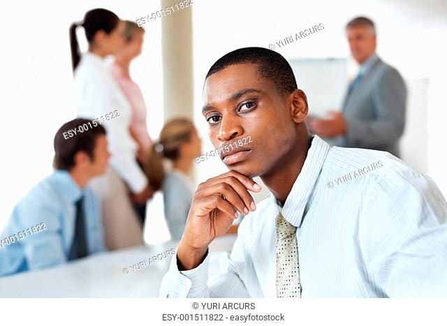 Serious business man looking at you with colleagues in background during a presentation