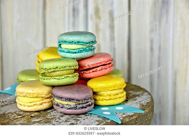 Colorful stack of French macaroons on a turquoise and white polka dot ribbon