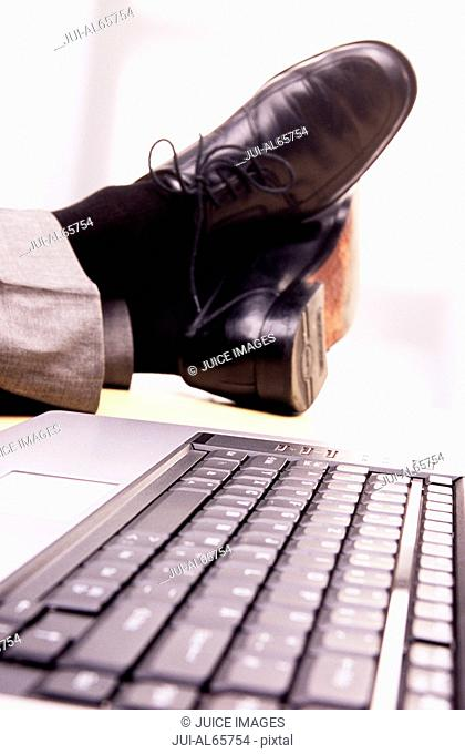 Businessman with feet up on desk next to laptop