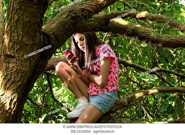 Teenage girl on her mobile phone in the park