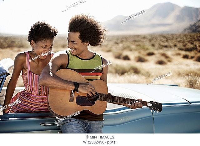 A young couple standing by a pale blue convertible on the open road, the man playing a guitar