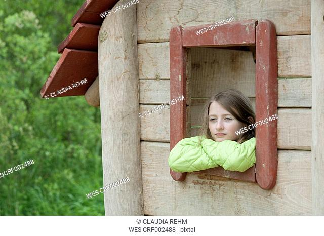 Germany, Bavaria, girl looking outside of the window of a wendy house