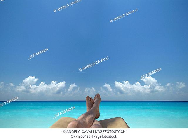 Man feet on a beach chair on a beach over blue ocean