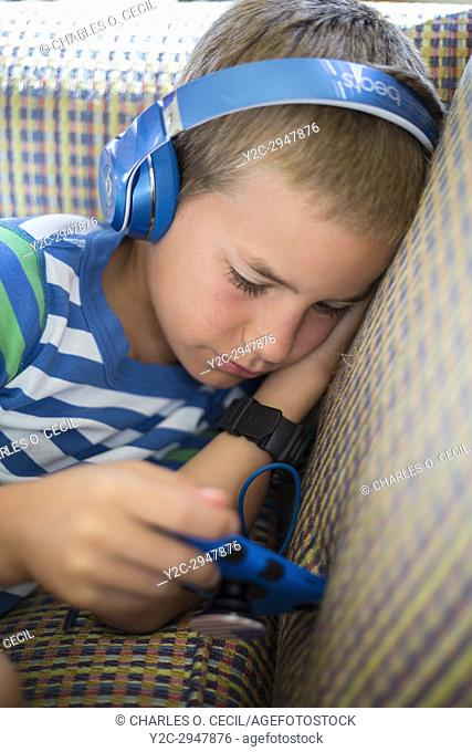 Avon, Outer Banks, North Carolina, USA. Young American Boy Playing with his Mobile Game Device