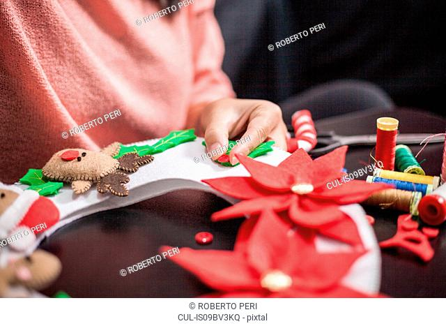 Woman stitching holly berry onto christmas decoration, mid section