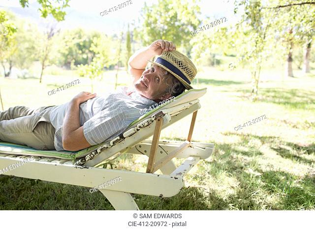 Older man relaxing on lawn chair outdoors