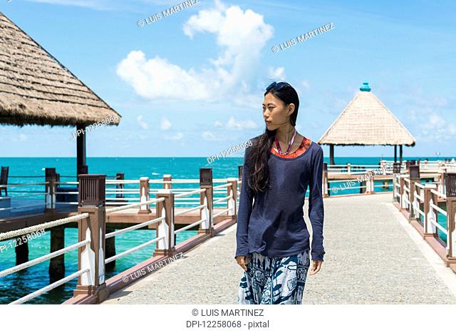 A young woman walks on the pier at Independence Beach; Sihanoukville, Cambodia