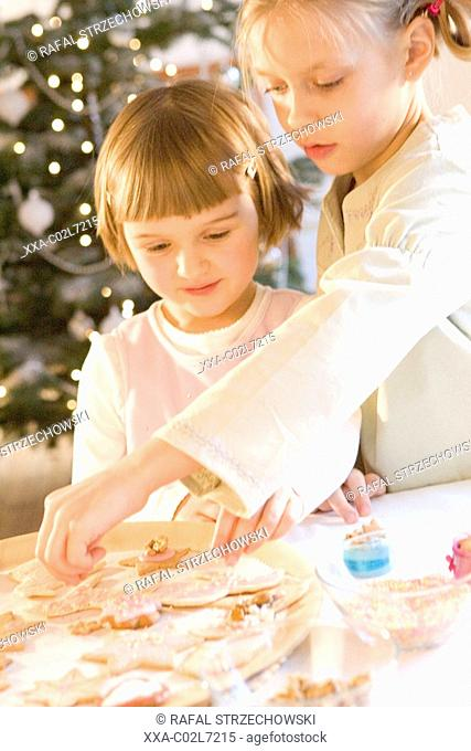 two girls making christmas cookies