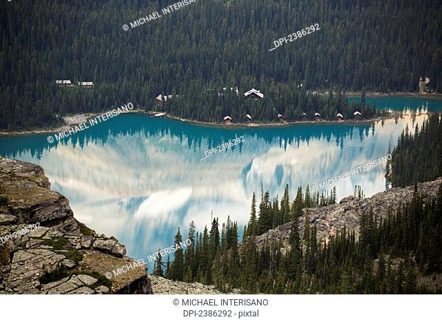 Alpine lake framed by shoreline and mountain cliffs and reflecting the mountains; British Columbia, Canada