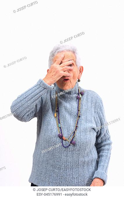 senior woman peeking with hand on face on white background