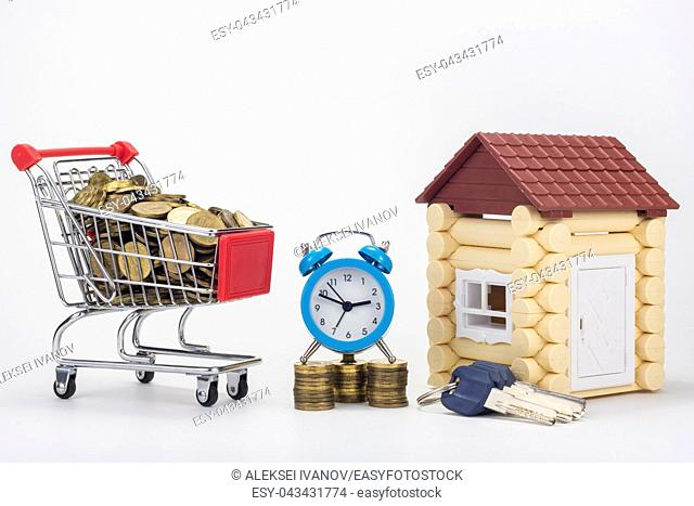 A grocery cart filled with coins, a desk clock, a bunch of keys and a playhouse