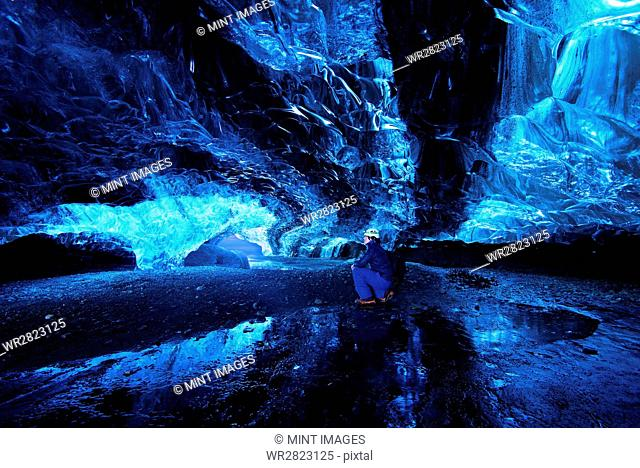 A person crouched down in an ice cavern wearing protective headgear, looking around at the walls of ice and rock