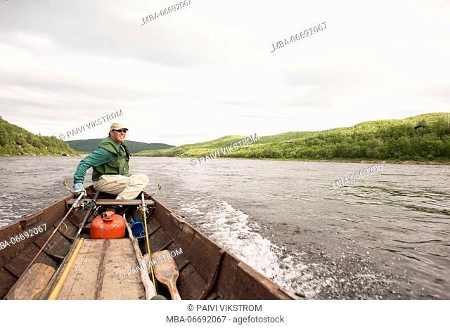 Fisher man with boat on the Tana river, Utsjoki, Lapland