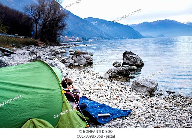Boy sitting on blanket by tent drinking coffee on lakeside, Lake Como, Onno, Lombardy, Italy