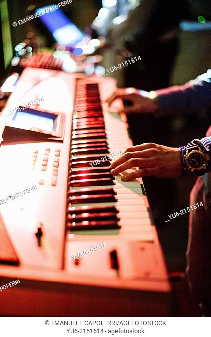 Hands of keyboardist with colored lights