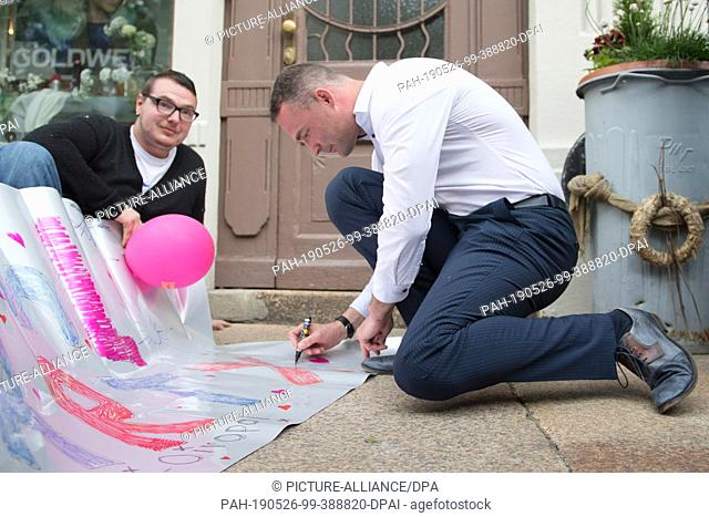 26 May 2019, Saxony, Görlitz: Sebastian Wippel (r), AfD Member of State Parliament and Lord Mayor candidate for Görlitz, signs a poster from a group of students