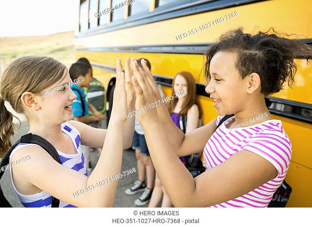 Happy schoolgirls playing patty cake by bus during field trip