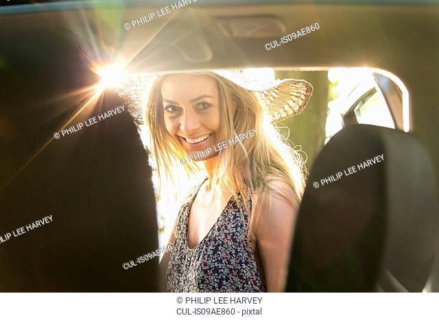 Portrait of young woman by car
