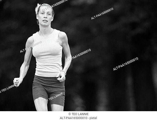 Woman in sports clothes running, three quarter length, b&w