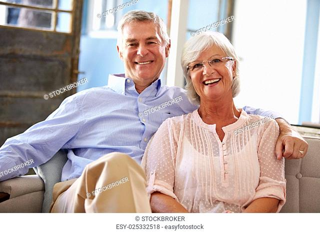 Portrait Of Smiling Senior Couple Sitting On Sofa At Home