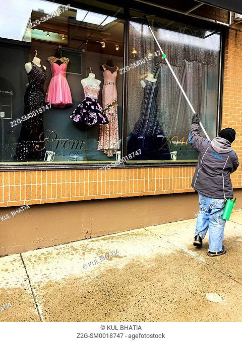 Window washer. A man washes the display window of a ladies' clothing store, Halifax, Canada