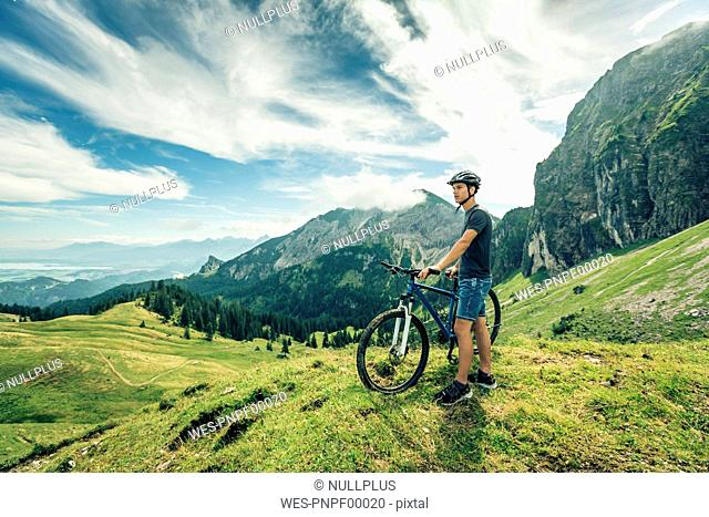 Germany, Bavaria, Pfronten, young man with mountain bike on alpine meadow near Aggenstein