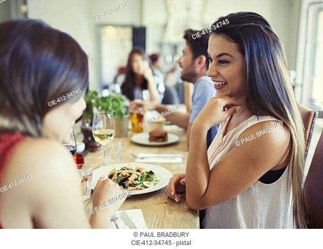 Smiling women friends talking and eating at restaurant table