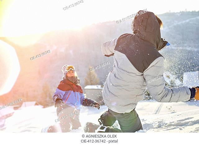 Playful couple enjoying snowball fight in sunny snowy field