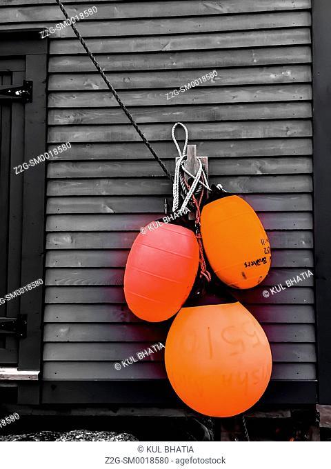 Selective colour -- three orange buoys on a dark grey shed -- full colour image simplified to two colours, Nova Scotia, Canada