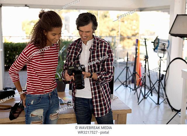 Photographer showing photos to fashion model on digital camera
