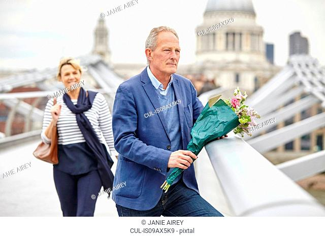 Mature man with bouquet waiting in front of date on Millennium Bridge, London, UK