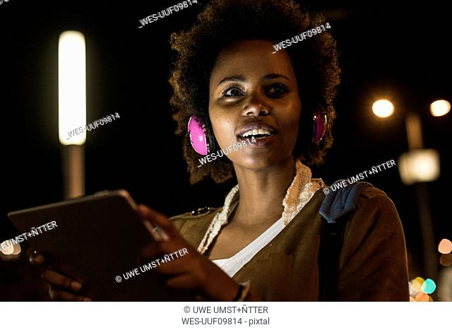 Portrait of young woman with headphones and tablet by night