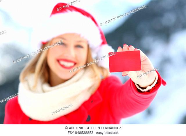 Front view portrait of a woman showing a blank credit card in christmas holidays with a snowy mountain in the background
