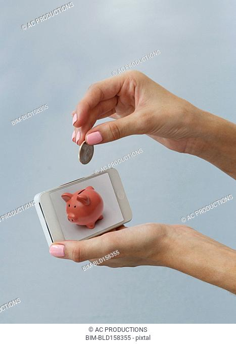 Caucasian woman depositing coin in cell phone piggy bank