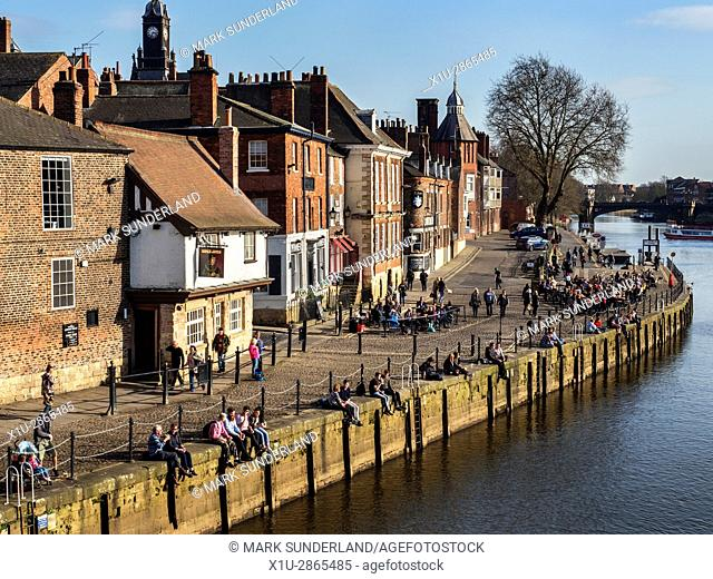 People Sitting in Spring Sunshine Outside Bars on Kings Staith by the River Ouse York Yorkshire England