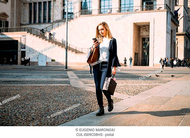 Young woman strolling in city square looking at smartphone