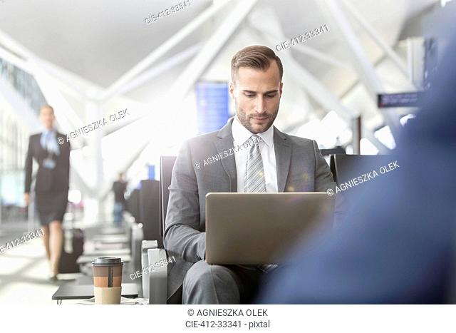 Businessman working using laptop in airport departure area